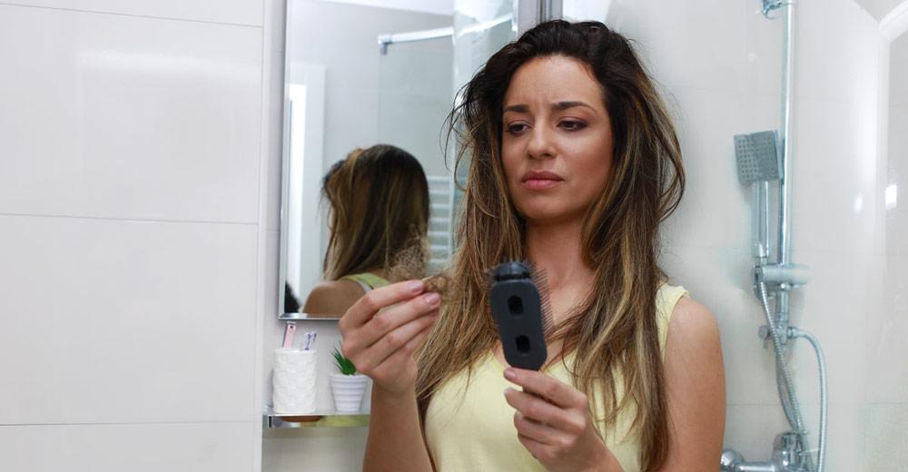 devojka drži u ruci kosu koja je opala